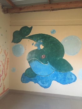 Jemella painted ocean mammals at either end of the playroom. On one end, a dolphin, and on this end, a whale.